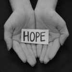 """hands holding a card bearing the word """"HOPE"""""""