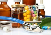 small bottles of pills and liquids all encircled by a stethoscope