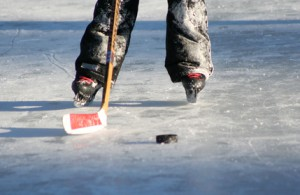 person's feet in hockey skates on ice