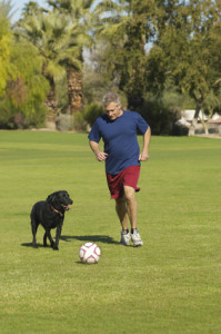 Man playing soccer with his dog