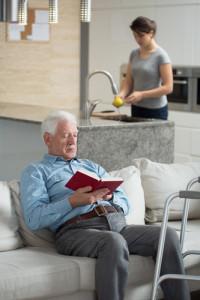 man reading, caretaker in background