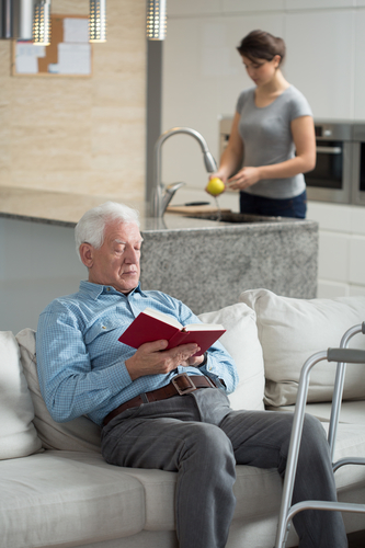 Man reading, caregiver in background